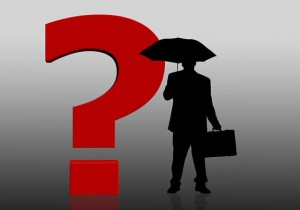 A man with an umbrella standing next to question mark.