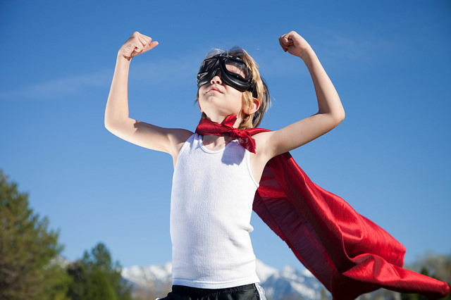 A young boy acting confident in a cape and eye googles.