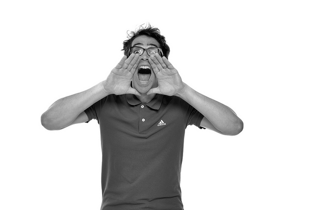 A man in glasses shouting.