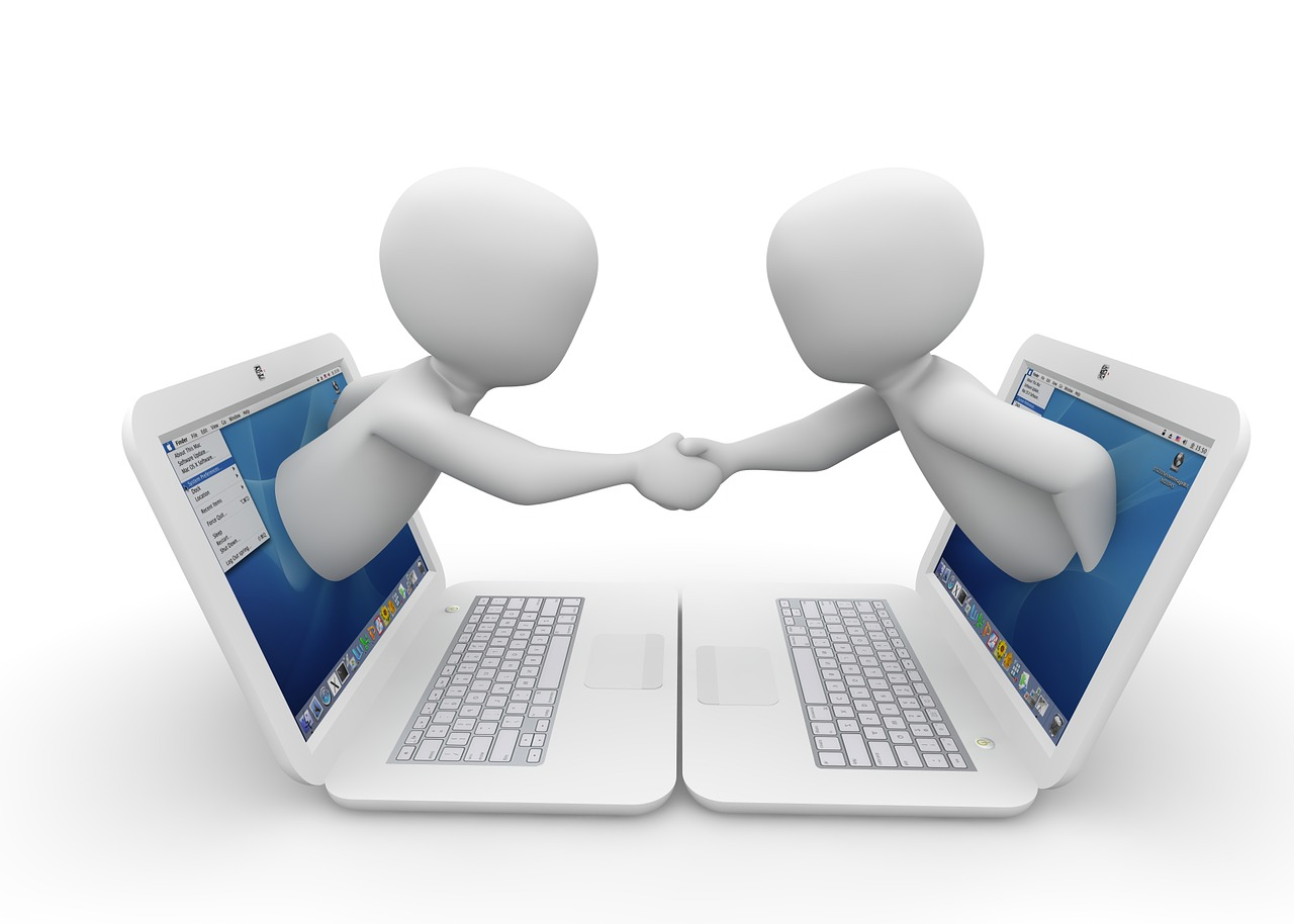 Two figures emerging from two computers and shaking hands.